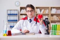 Le docteur de super héros travaillant dans l'hôpital de laboratoire Image stock