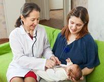 Le docteur des enfants examinant la chéri nouveau-née Photo stock