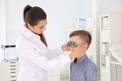 Le docteur des enfants mettant le cadre d'essai sur peu de gar?on dans la clinique photographie stock