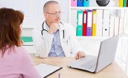 Le docteur donne à patient féminin les résultats de son analyse image libre de droits