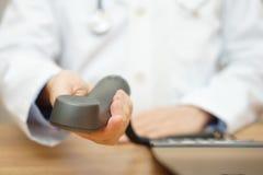 Le docteur donne le casque de téléphone au patient, docteur d'appel concentré Images libres de droits