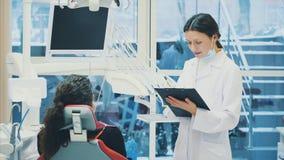 Le docteur enregistre les données ou l'histoire du patient de la maladie Rendez visite à un médecin ou à un dentiste à votre bure banque de vidéos