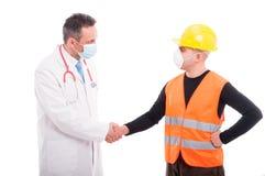 Le docteur et le constructeur se serrant la main aiment des amis Images stock