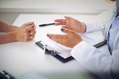 Le docteur et le patient discutent quelque chose, juste mains à la table Photo libre de droits