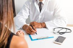 Le docteur et le patient discutent au sujet du diagnostic Médecin tenant un stéthoscope et prenant des notes images libres de droits