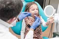 Le docteur examine des dents de l'enfant image libre de droits