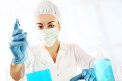 Le docteur examine l'échantillon sous un microscope Photographie stock libre de droits