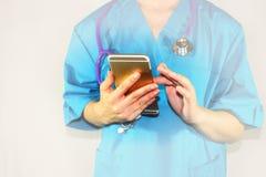 Le docteur examine sur le smartphone l'appel du patient, l'attention prend soin de la recette photos libres de droits