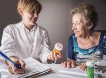 Le docteur explique à la dose quotidienne de personnes âgées de médicament image stock