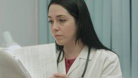 Le docteur féminin dans le bureau médical analyse des résultats un électrocardiogramme et prend des notes Photographie stock libre de droits