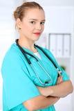 Le docteur féminin de chirurgien se tient avec des bras croisés et sourit à l'hôpital Médecin prêt à examiner le patient photos stock