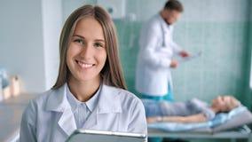 Le docteur féminin de sourire dans le laboratoire blanc enduisent à l'aide de la tablette préparant le patient pour la procédure banque de vidéos