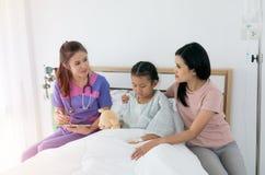 Le docteur féminin parle à la mère patiente du ` s images stock