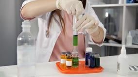 Le docteur féminin prenant le médicament dans une seringue et la prépare pour l'injection banque de vidéos