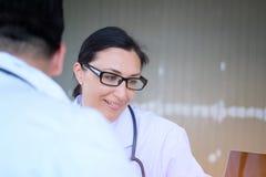 Le docteur féminin supérieur consulte le jeune patient s'asseyant au docteur de image libre de droits