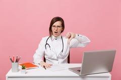 Le docteur féminin triste fatigué s'assied au travail de bureau sur l'ordinateur avec le document médical dans l'hôpital d'isolem photo libre de droits