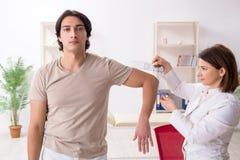 Le docteur f?minin v?rifiant la flexibilit? commune du patient avec le goniom?tre images libres de droits