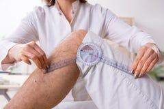 Le docteur f?minin v?rifiant la flexibilit? commune du patient avec le goniom?tre photographie stock libre de droits