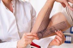 Le docteur f?minin v?rifiant la flexibilit? commune du patient avec le goniom?tre photographie stock