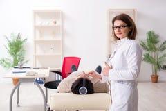 Le docteur f?minin v?rifiant la flexibilit? commune du patient avec le goniom?tre photos libres de droits