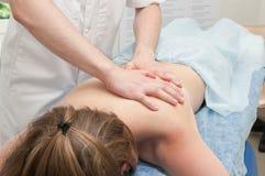 Le docteur fait un massage de corps à une fille photos libres de droits
