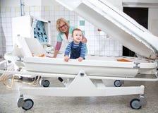 Le docteur féminin examine le petit garçon dans la chambre de pression Photos libres de droits