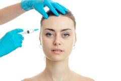 Le docteur injecte le vaccin sur le front à de jeunes filles sans plan rapproché de maquillage photographie stock libre de droits