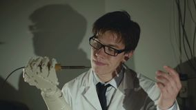 Le docteur lève la prothèse de main avec le fer à souder, la touche et consomme banque de vidéos