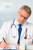 Le docteur mûr prescrit l'examen médical Photo stock