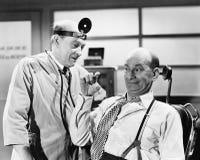 Le docteur masculin écoutant un homme qui explique quelque chose avec ses doigts (toutes les personnes représentées ne sont pas p Images libres de droits