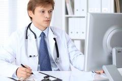 Le docteur masculin amical s'assied à la table et travaille dans le bureau d'hôpital Préparez pour examiner et aider des patients photos stock