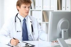 Le docteur masculin amical s'assied à la table et travaille dans le bureau d'hôpital Préparez pour examiner et aider des patients images stock