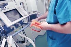 Le docteur masculin avec des électrodes de défibrillateur dans sa main place le d Image stock