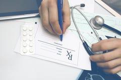 Le docteur masculin complète la forme de prescription après examen de photographie stock libre de droits