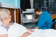 Le docteur masculin dans l'uniforme regarde le moniteur du dispositif médical W Photographie stock libre de droits