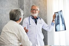 Le docteur masculin et le patient asiatique examinent le film radiographique ensemble photographie stock libre de droits