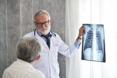 Le docteur masculin et le patient asiatique examinent le film radiographique ensemble image stock