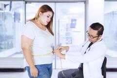 Le docteur masculin examine une femme obèse dans l'hôpital photographie stock libre de droits