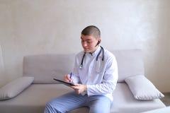 Le docteur masculin moderne parle au patient par le bluetooth et écrit à r Photographie stock libre de droits