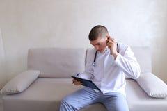 Le docteur masculin moderne parle au patient par le bluetooth et écrit à r Photos libres de droits