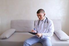 Le docteur masculin moderne parle au patient par le bluetooth et écrit à r Images stock