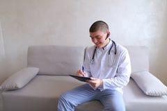 Le docteur masculin moderne parle au patient par le bluetooth et écrit à r Image stock