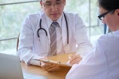Le docteur masculin supérieur consulte le jeune patient s'asseyant à l'offi de docteur photographie stock libre de droits