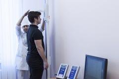 Le docteur mesure la croissance du bureau médical photographie stock libre de droits