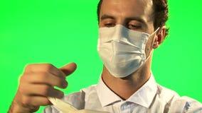 Le docteur met dessus le masque et les gants chirurgicaux - écran vert banque de vidéos