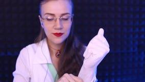 Le docteur met dessus ses gants en caoutchouc de mains banque de vidéos