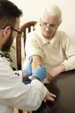 Le docteur met une aiguille dans la veine de dame âgée Photographie stock libre de droits