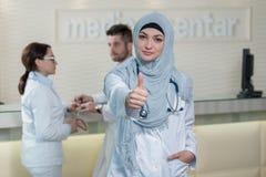 Le docteur musulman féminin gai de sourire heureux avec des pouces lèvent le geste Image stock