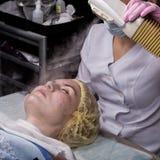 Le docteur nettoie la peau de la femme avec une vapeur jeune femme avec la peau de probl?me ? l'esth?ticien Concept de cosm?tolog images stock