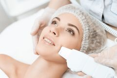 Le docteur nettoie la peau du ` s de femme avec un dispositif médical spécial La femme est venue à la procédure de l'épilation de photo libre de droits
